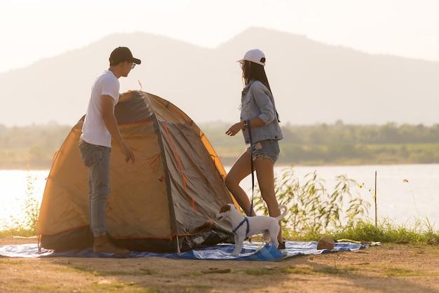 젊은 성인 아시아 부부 피치와 호수 주변 캠핑을 위해 텐트를 설정합니다.