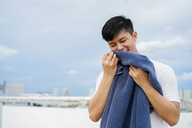 Young adult asian man smelling the blue towel at outside home after for daily and routine
