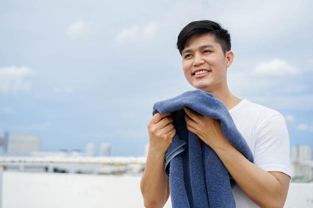 Молодой взрослый азиатский мужчина нюхает синее полотенце вне дома после повседневной и рутинной работы