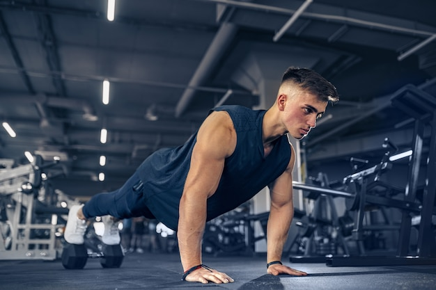 Young adult athlete doing push ups as part of bodybuilding training.