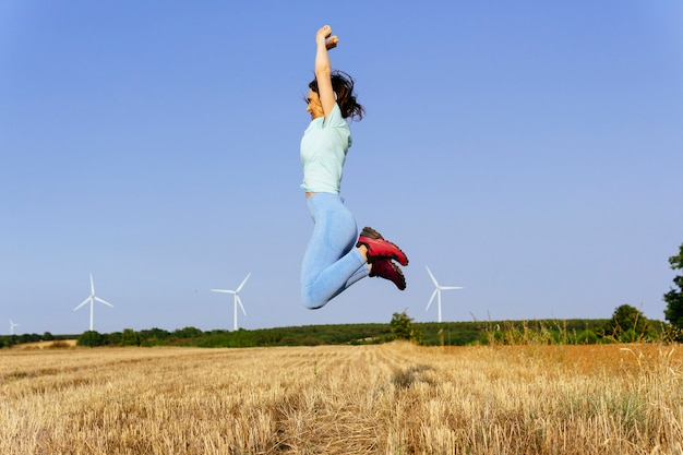 Young adult athlete jogger woman jumping happy with raised arms. success concept