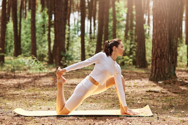 Young adult attractive female in white sportswear practicing yoga on karemat on open air in green forest, workout, sporty female enjoying training on nature.