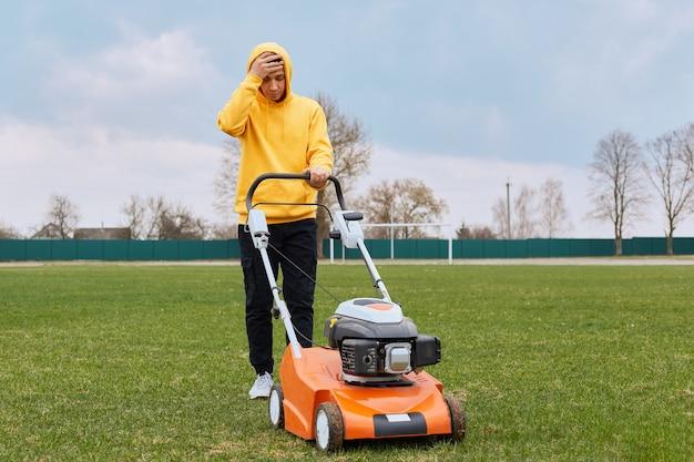 若い大人の魅力的な庭師は、広いフィールドで芝生を刈り取ります