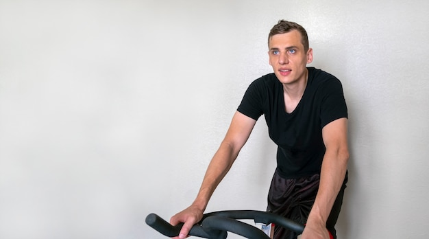 Young adult attractive man engaged on a house bike on a white background, copy space