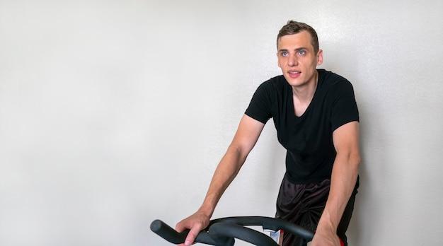 白い背景に、コピー領域の家の自転車に従事している若い大人の魅力的な男性