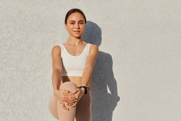 Young adult attractive woman wearing white sporty top standing keeping hands on knee, stretching leg before or after sports exercises, healthy lifestyle.