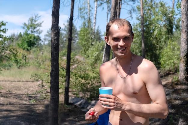 젊은 성인 맨발 -chested 남자는 더운 여름 날에 자연에서 휴가를 즐깁니다. 그는 나무의 배경에 유리와 체리를 들고 미소 짓는다.