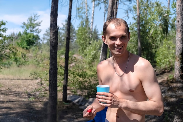 Young adult bare-chested man enjoys a vacation in nature on a hot summer day. he smiles holding a glass and cherry in the background of the trees
