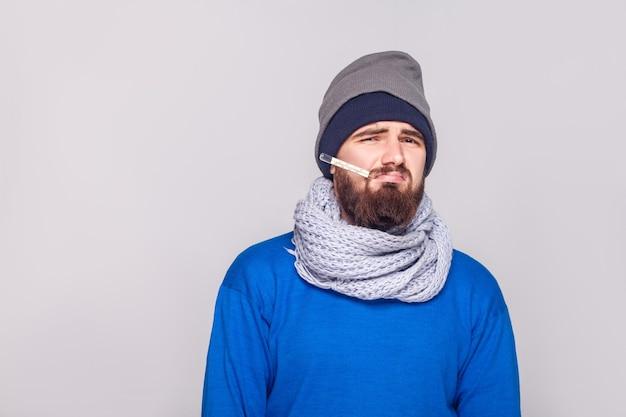 若い大人のひげを生やした男性は、温度計を口の中に持って、体温を持っています。スタジオショット、灰色の背景に分離