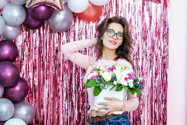 お祝いの背景に花の肖像画を保持している若い大人の美しく幸せな女性モデル