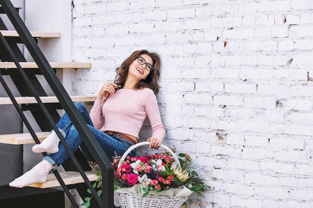 明るい階段の上の彼女の手の肖像画に花を持つ若い大人の美しく幸せな女性モデル