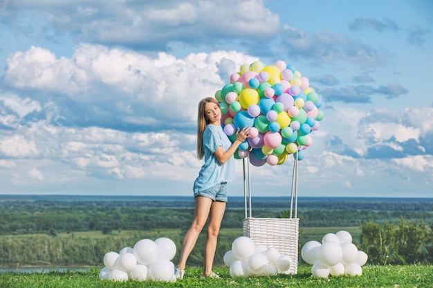 Young adult beautiful blonde girl happy on green grass with balloon airship on blue sky
