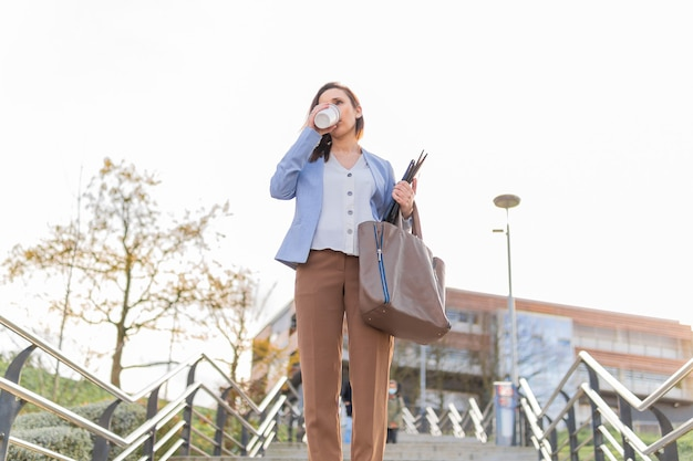 Молодой взрослый красивый предприниматель, пить кофе на улице, оставив работу с кофе, чтобы пойти в ноутбук и папку. концепция успешной деловой женщины. копией пространства