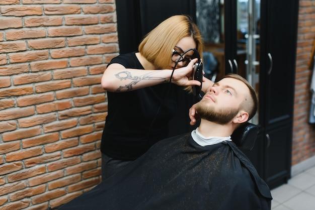 若い大人の美しい白人女性の美容師は、現代の理髪店でひげのハンサムな男をカットします幸せなゲイの座っている椅子の男性の美容院。