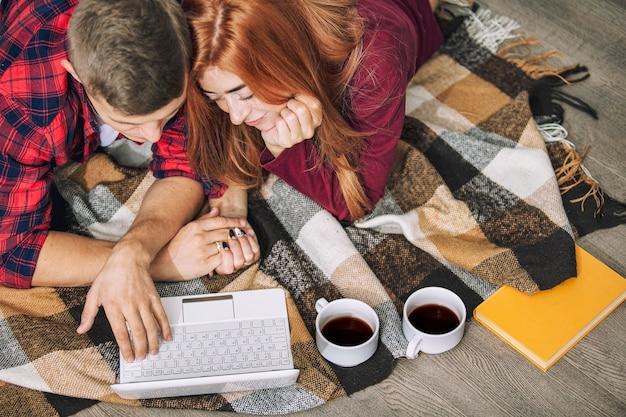 コンピューターと自宅で恋をしている若い大人の美しいカップル