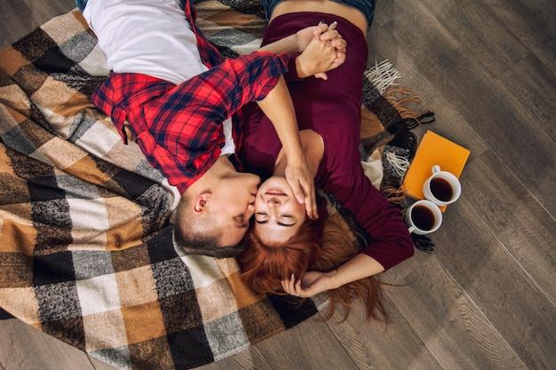 自宅で恋をしている若い大人の美しいカップル