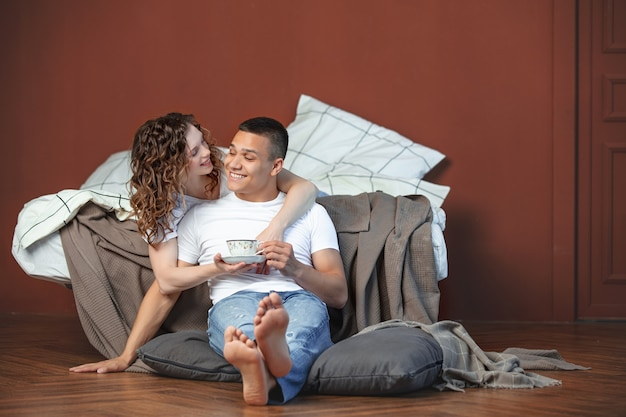 Young adult beautiful couple in love, man and woman together in bedroom home interior