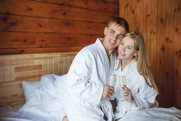 Молодой взрослый красивая счастливая пара мужчина и женщина с бокалами белого вина в спальне