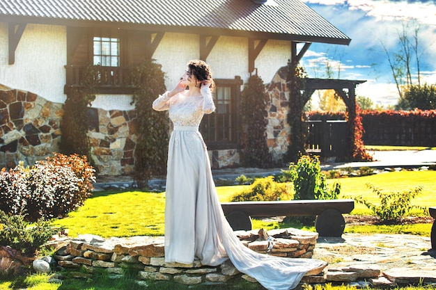 Young adult beautiful happy woman in a beautiful dress on the background of a beautiful house