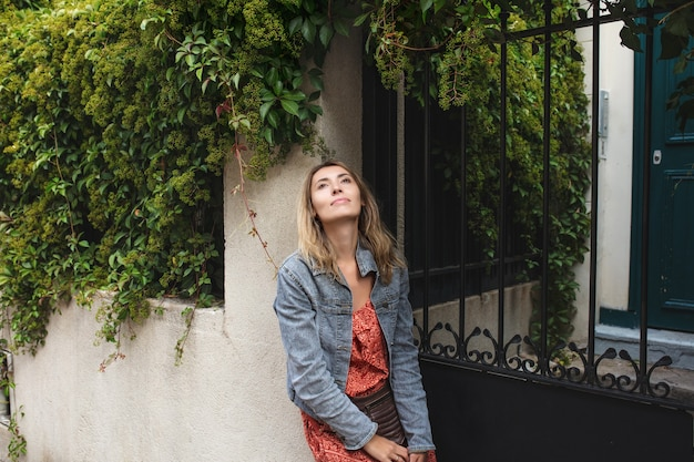 ヨーロッパの街を歩き回るカジュアルなスタイルの若い大人の美しい幸せな女性