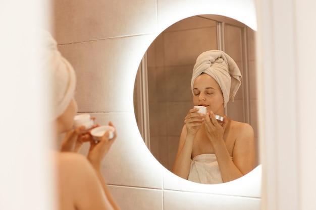 젊은 성인 미녀는 거울 앞에 있는 욕실 머리에 하얀 수건을 얹고 서서 크림 냄새를 맡고, 적용하기 전에 크림 냄새를 맡습니다.