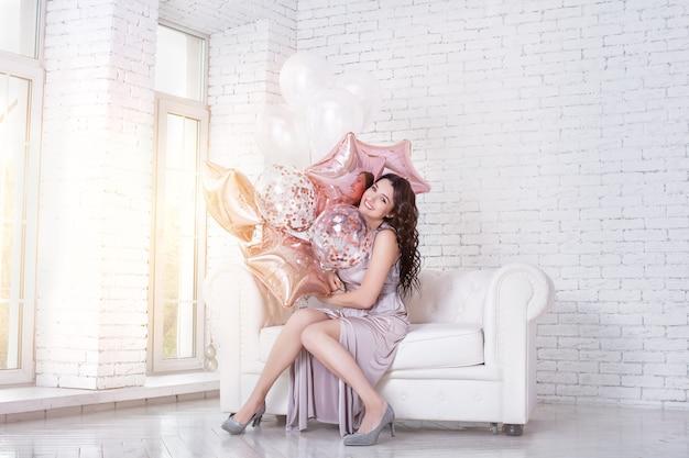 白いソファの上にピンクの風船と長いファッショナブルなお祝いのドレスを着た若い大人の美しい女性