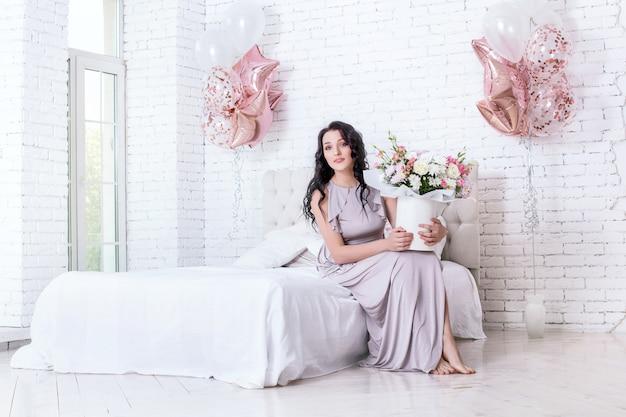 침실에 풍선과 꽃이 있는 길고 세련된 휴가 드레스를 입은 젊은 성인 아름다운 여성