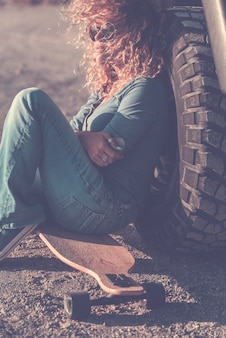 若い大人の美しい女性が背中のロングボードスケートと車のホイールで道路に座る-旅行の概念とアウトドアでアクティブなスタイリッシュなライフスタイルの人々-女性の冒険旅行生活 Premium写真