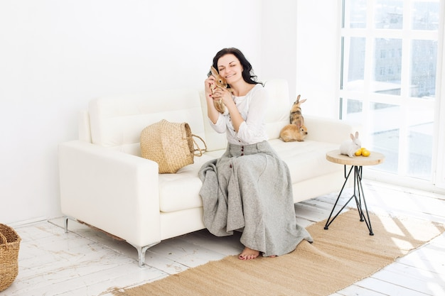 Young adult beautiful woman with fluffy rabbits and easter eggs sitting on a white sofa