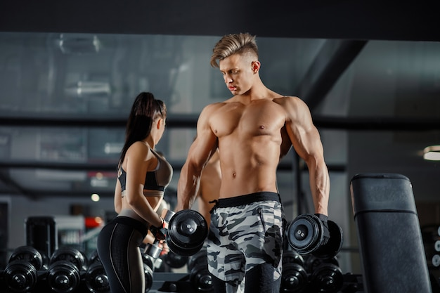 Young adult bodybuilder and girl model doing weightlifting in the gym near the mirror