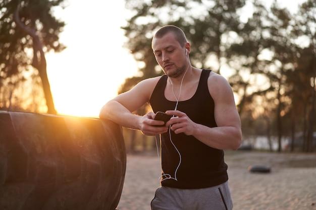 トレーニング後に電話音楽の白いヘッドフォンを聞いている若い大人の白人アスリート。