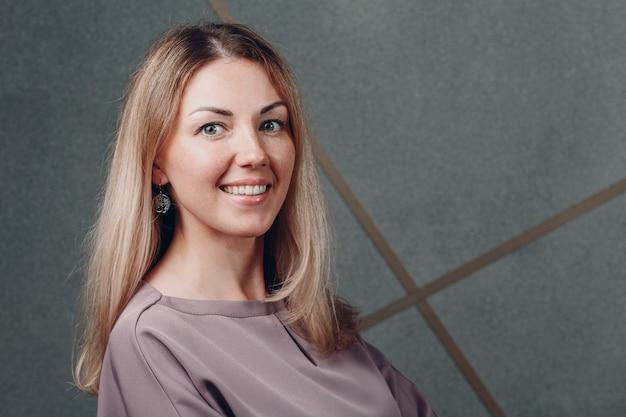 Молодой взрослый кавказской европейской блондинки улыбается женщина половину поворота лицо портрет.