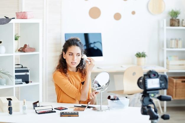 カメラでカジュアルなメイクや録音プロセスを行う若い大人の白人女性