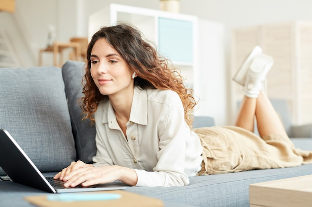 집에서 소파에서 휴식을 취하는 동안 원격 작업을 위해 그녀의 노트북을 사용하는 젊은 성인 백인 여자