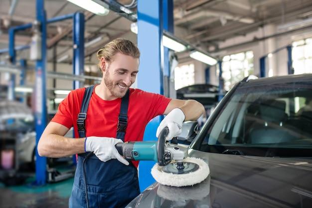 Молодой взрослый уверенный в себе человек в рабочей форме, работающий на автомобилях