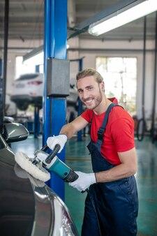 車に取り組んで作業服の若い大人の自信を持って男