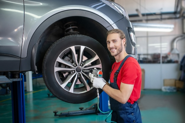 Young adult confident man in work uniform working on cars
