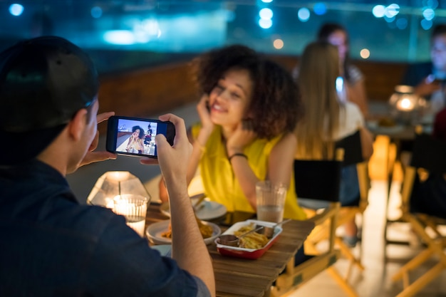 Young adult couple on a dinner date taking smartphone photos