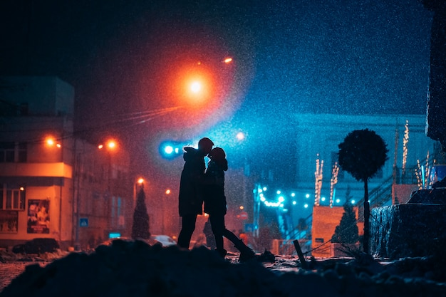 雪に覆われた通りでお互いの腕の中で若い大人2名様