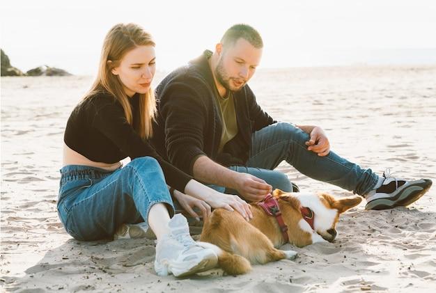 若い大人のカップルはビーチとふれあい犬の砂の上に座っています。自然の中のカジュアルな服装で歩く