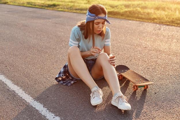 Giovane donna adulta dai capelli scuri seduta su una strada asfaltata dopo essere caduta dallo skateboard, ferita al ginocchio, sentendo dolore, guardando la gamba con il viso accigliato.