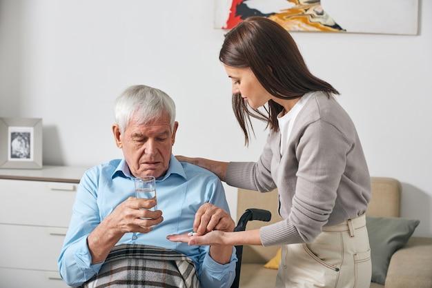 Молодая взрослая дочь дает таблетки старшему отцу, заботясь о нем после инсульта