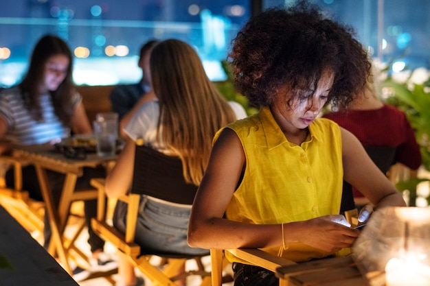 Young adult on a dinner date using a smartphone addiction concept