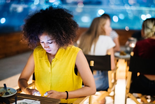 Young adult on a dinner date using a smartphone addiction