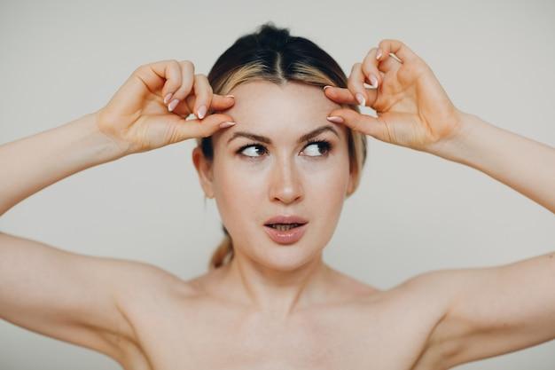 얼굴 체조 자기 마사지를하고 젊어지게하는 젊은 성인은 피부와 근육 리프팅을위한 건물에 직면 해 있습니다.