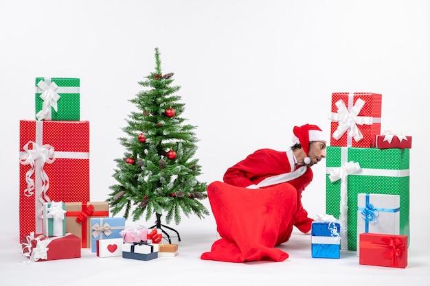 Молодой человек в костюме санта-клауса с подарками и украшенной елкой сидит в земле и что-то ищет