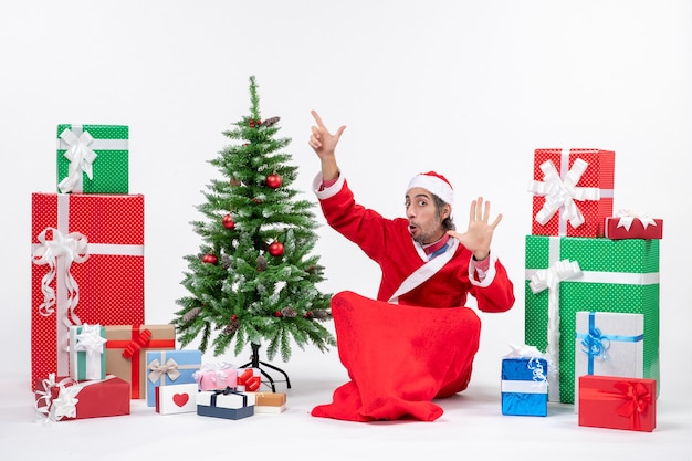 Young adult dressed as santa claus with gifts and decorated christmas tree sitting in the ground pointing above showing five