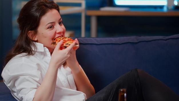 ソファに座ってピザとビールのスライスを楽しんでいる若い大人