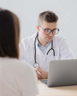 A young adult european and competent doctor in a white coat in a medical clinic in his office is
