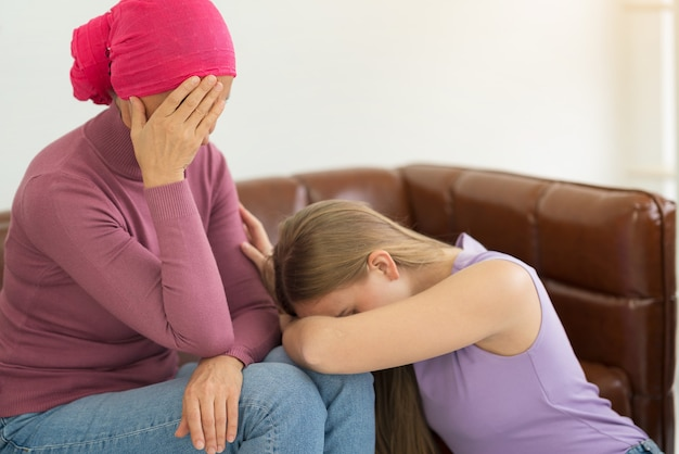 Young adult female cancer patient spending time with her daughter at home.